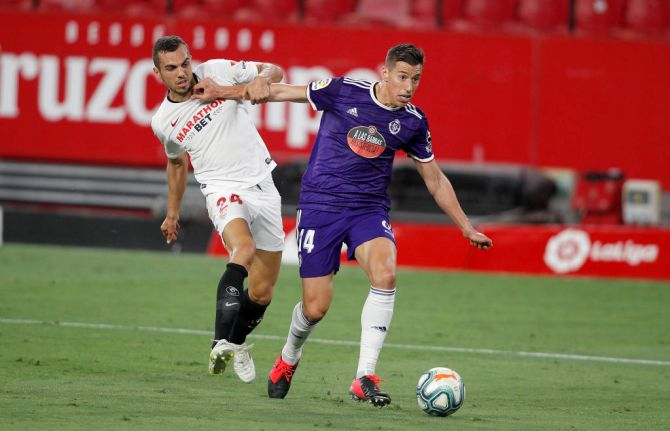 Sevilla's Joan Jordán challenges Valladolid's Ruben Alcaraz during their La Liga match at Estadio Ramon Sanchez Pizjuan in Seville, Spain