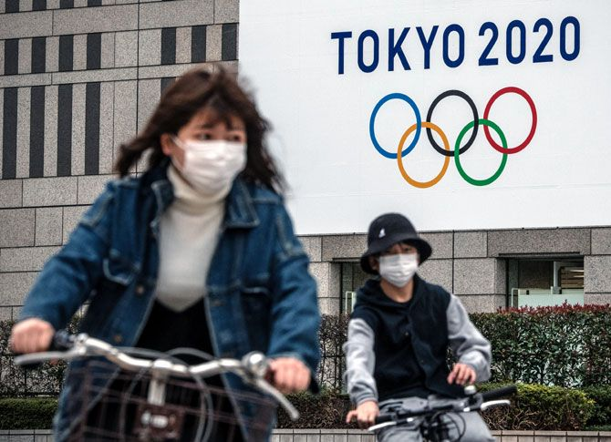 People wearing masks cycle past a banner for the Tokyo Olympics in Tokyo.  At his first remote news conference on Friday, Tokyo 2020 CEO Toshiro Muto emphasized that Games organisers were aiming towards the new start date of July 23, 2021, regardless of how long it takes to contain the coronavirus outbreak.