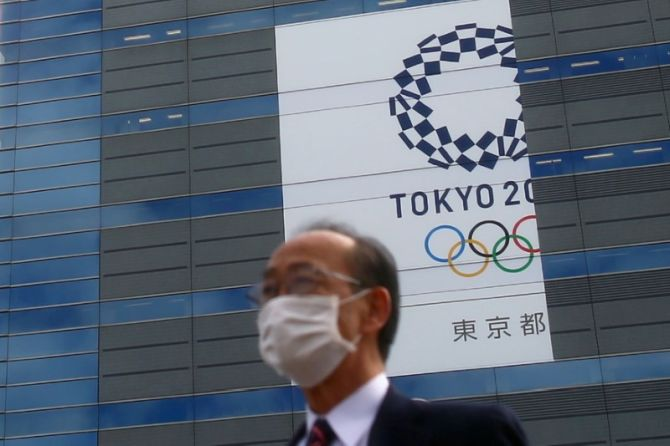 A man, wearing a protective mask following an outbreak of the coronavirus disease (COVID-19) is pictured in front of a banner for the upcoming Tokyo 2020 Olympics in Tokyo, Japan, on March 12, 2020. (Image used for representational purposes)