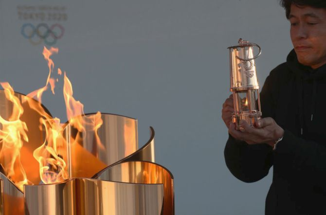 A staff preserves the Olympic flame to the lantern during the 'Flame of Recovery' special exhibition at Aquamarine Park in Iwaki, Fukushima, Japan, on Wednesday, March 25, a day after the postponement of the Tokyo 2020 Olympic and Paralympic Games was announced due to the coronavirus pandemic