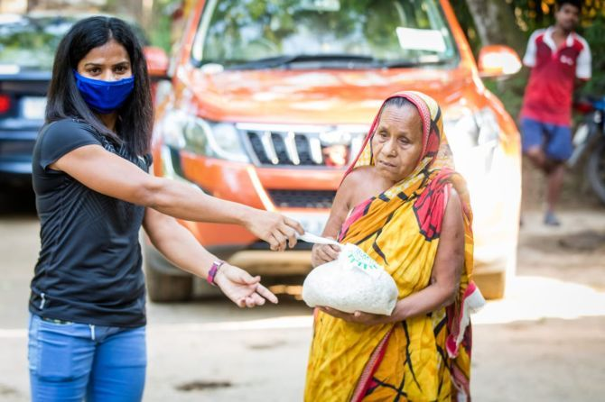 India's sprint queen Dutee Chand distributes food items to the needy in her village of Jajpur in Odisha
