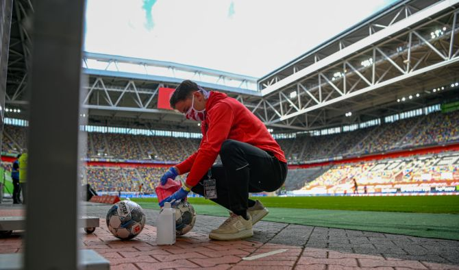 A staff member wipes down the footballs with a cloth so they are disinfected during the Bundesliga match between Fortuna Duesseldorf and SC Paderborn 07 at Merkur Spiel-Arena in Duesseldorf, Germany, on Saturday