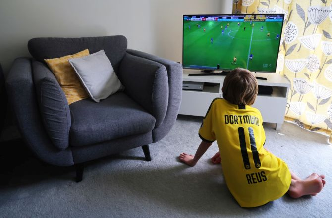 A young boy watches the Bundesliga match between Borussia Dortmund and FC Schalke 04 live on TV in Wallington, England on Saturday