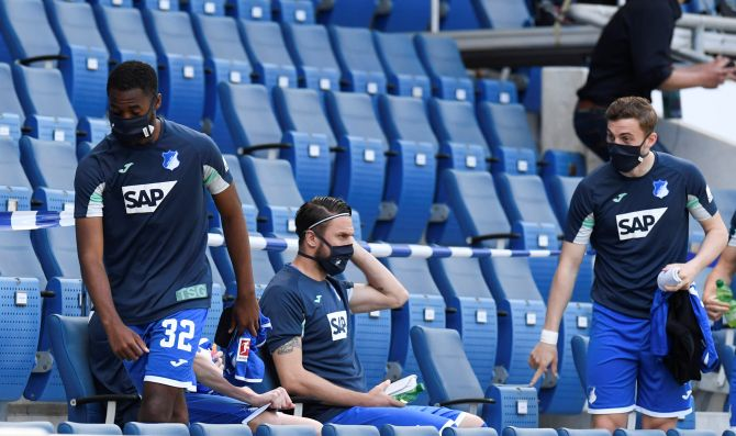 Hoffenheim substitutes wear protective face masks, as play between TSG 1899 Hoffenheim and Hertha BSC at the PreZero Arena, Sinsheim, in Germany resumes behind closed doors.