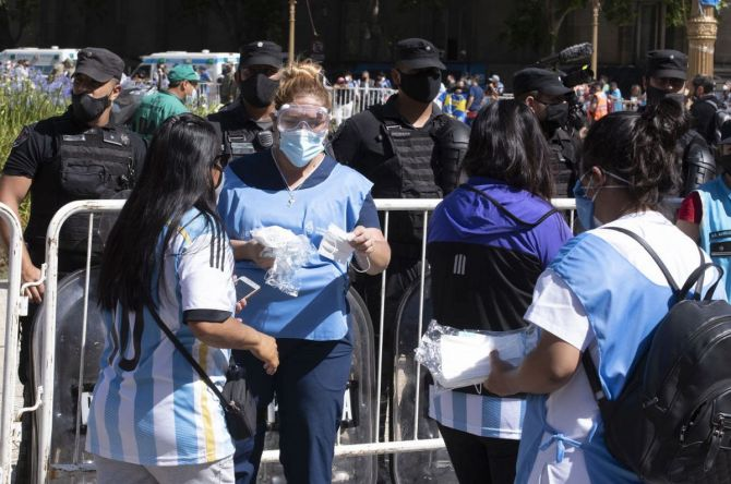 People offer masks as fans attend the funeral for Diego Maradaona at Casa Rosada