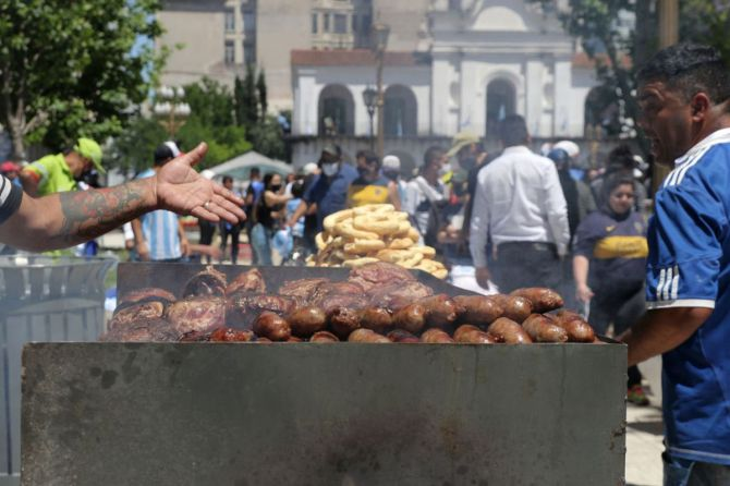 A street vendor offers sausage and meat during Diego Maradona's funeral in Buenos Aires on Thursday