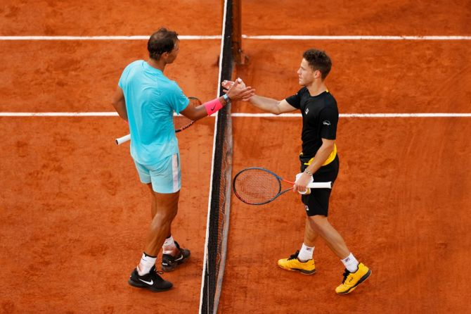 Rafael Nadal and Diego Schwartzman meet at the net after their match.