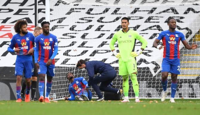 Wilfried Zaha receives medical assistance after getting injured while scoring Crystal Palace's second goal