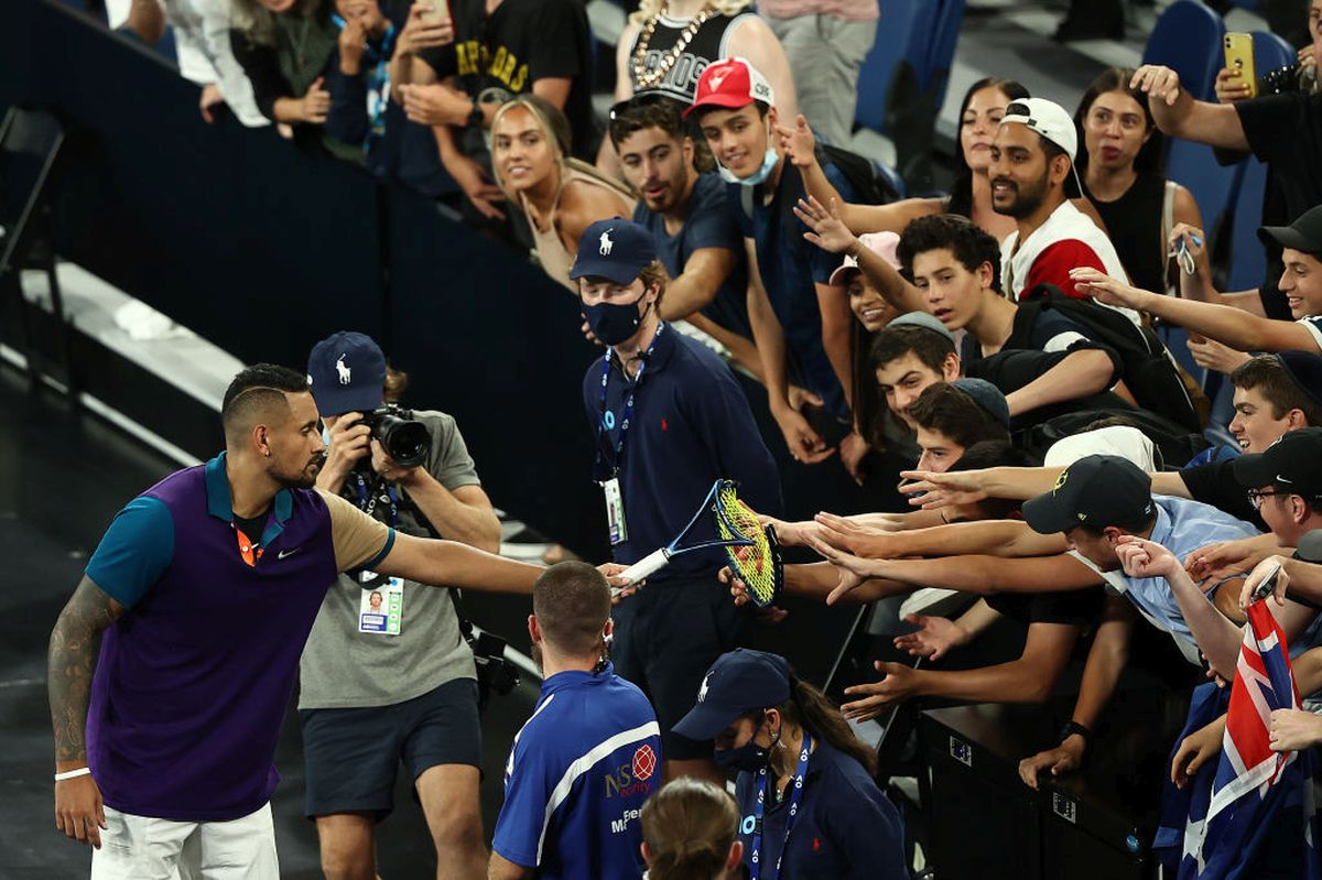 Australia's Nick Kyrgios gives his broken racket to fans after winning his Australian Open second round match against France's Ugo Humbert on Wednesday