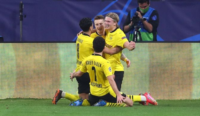 Borussia Dortmund's Erling Haaland (right) celebrates with Marco Reus and other team mates after scoring the third goal against Sevilla FC during their UEFA Champions League Round of 16 match at Estadio Ramon Sanchez Pizjuan in Seville