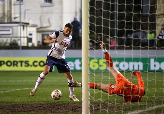 Carlos Vinicius takes the ball around goalkeeper Bayleigh Passant of Marine to score Tottenham Hotspur's first goal.
