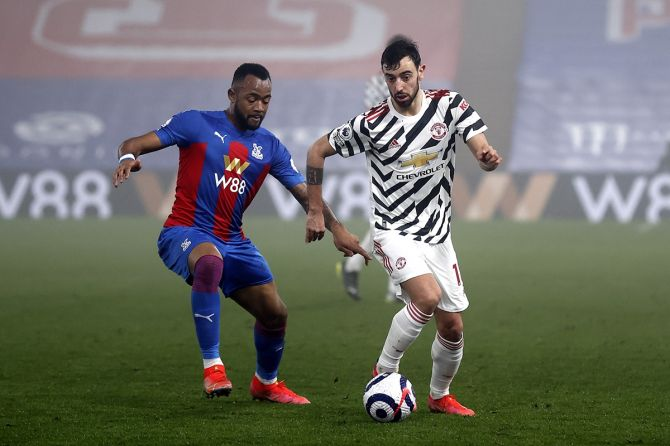 Manchester United's Bruno Fernandes battles for possession with Crystal Palace's Jordan Ayew.